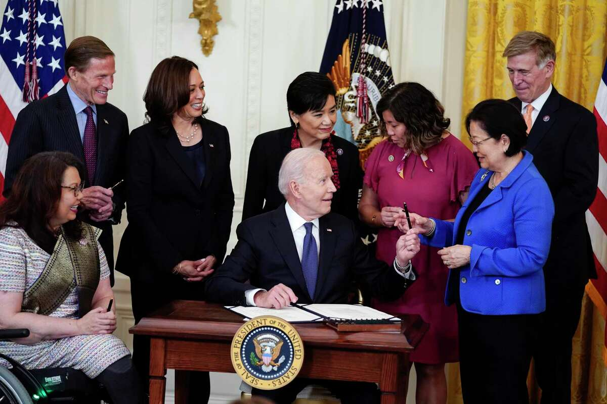 President Joe Biden hands out a pen to Sen. Mazie Hirono, D-Hawaii, after signing the COVID-19 Hate Crimes Act, in the East Room of the White House, Thursday, May 20, 2021, in Washington. (AP Photo/Evan Vucci)