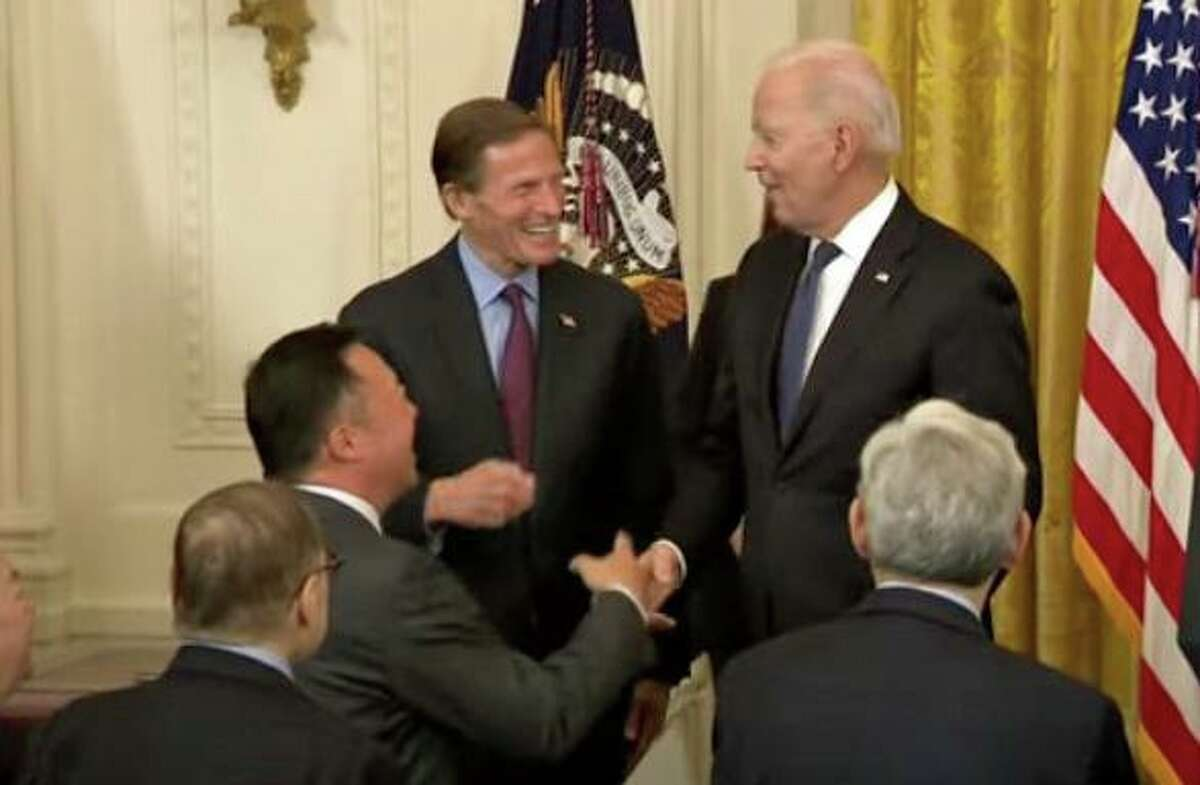 President Joe Biden (back right) spoke to Sen. Richard Blumenthal, D-Conn., (Back left) and Connecticut Attorney General William Tong (center left) after signing legislation aimed at reducing hate crimes against Asian Americans.