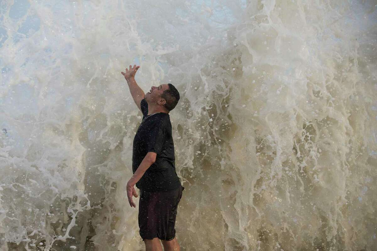 Water falls over Jimmy Villarreal, of Galveston, as a wave hits the seawall while he was watching the surf stirred up by Hurricane Laura Wednesday, Aug. 26, 2020 in Galveston.