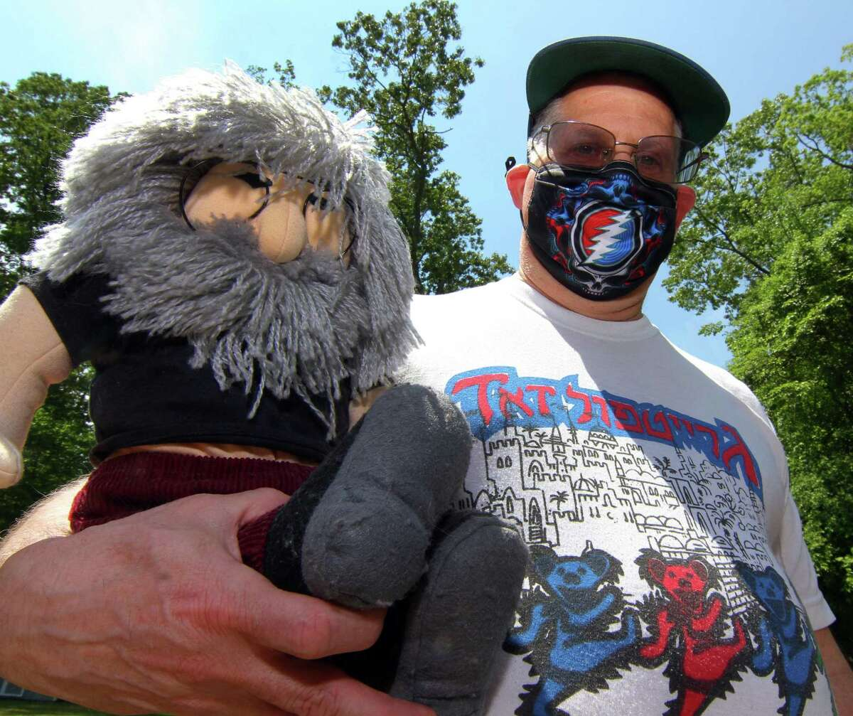 Jeff Pardo, who leads the Temple Heads - a group of Deadheads out of Temple Sinai in Stamford - poses with a Jerry Garcia doll at his home in Stamford, Conn., on Thursday May 20, 2021. Though his cadre of Jewish Dead lovers is skews secular, the Temple decided to put on a Dead-themed Shabbat service on Friday afternoon featuring Grateful Dead songs set to traditional music and vice versa.