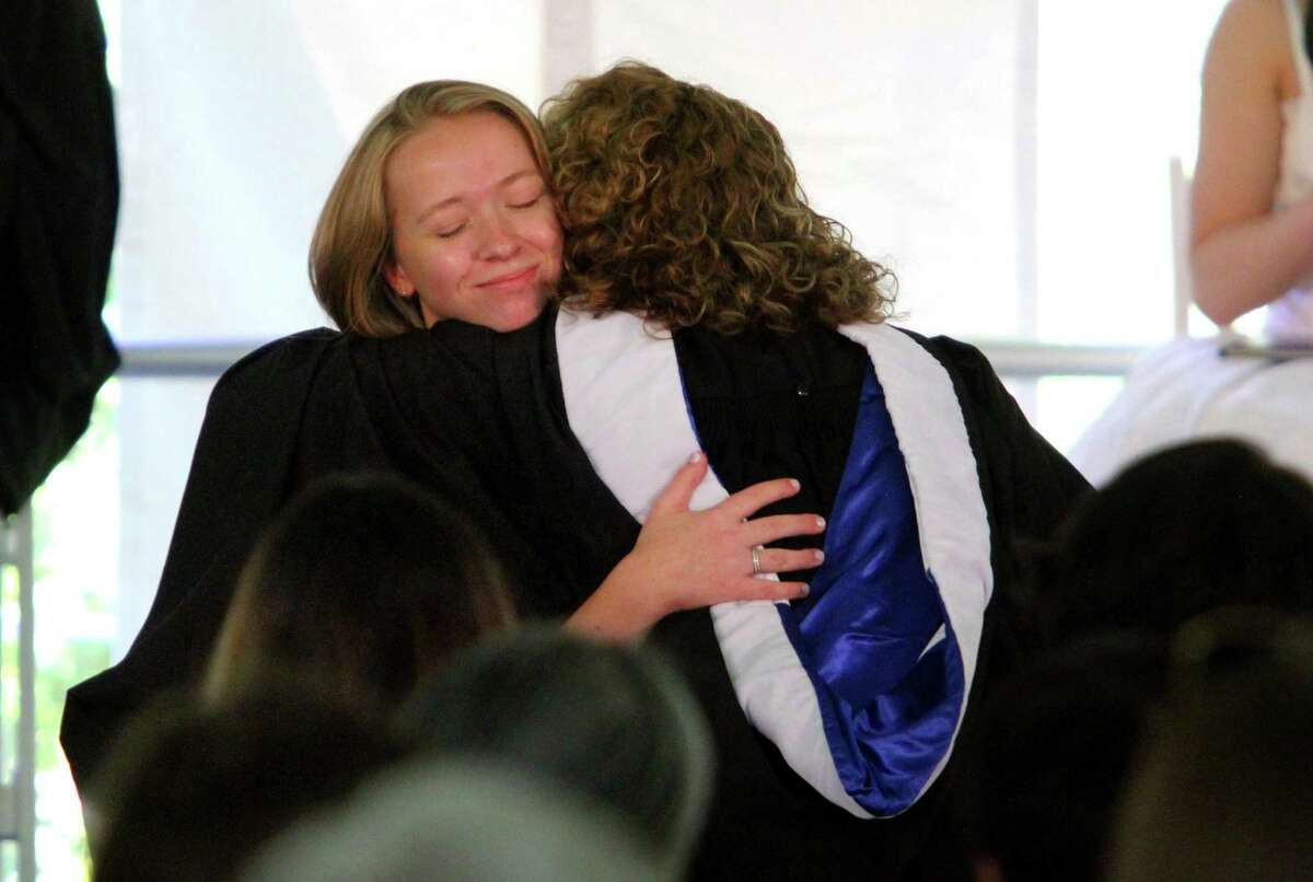 Lucy Meyer gets her diploma and a big hug from her mom, Dean of Seniors Mary Gayle Meyer.