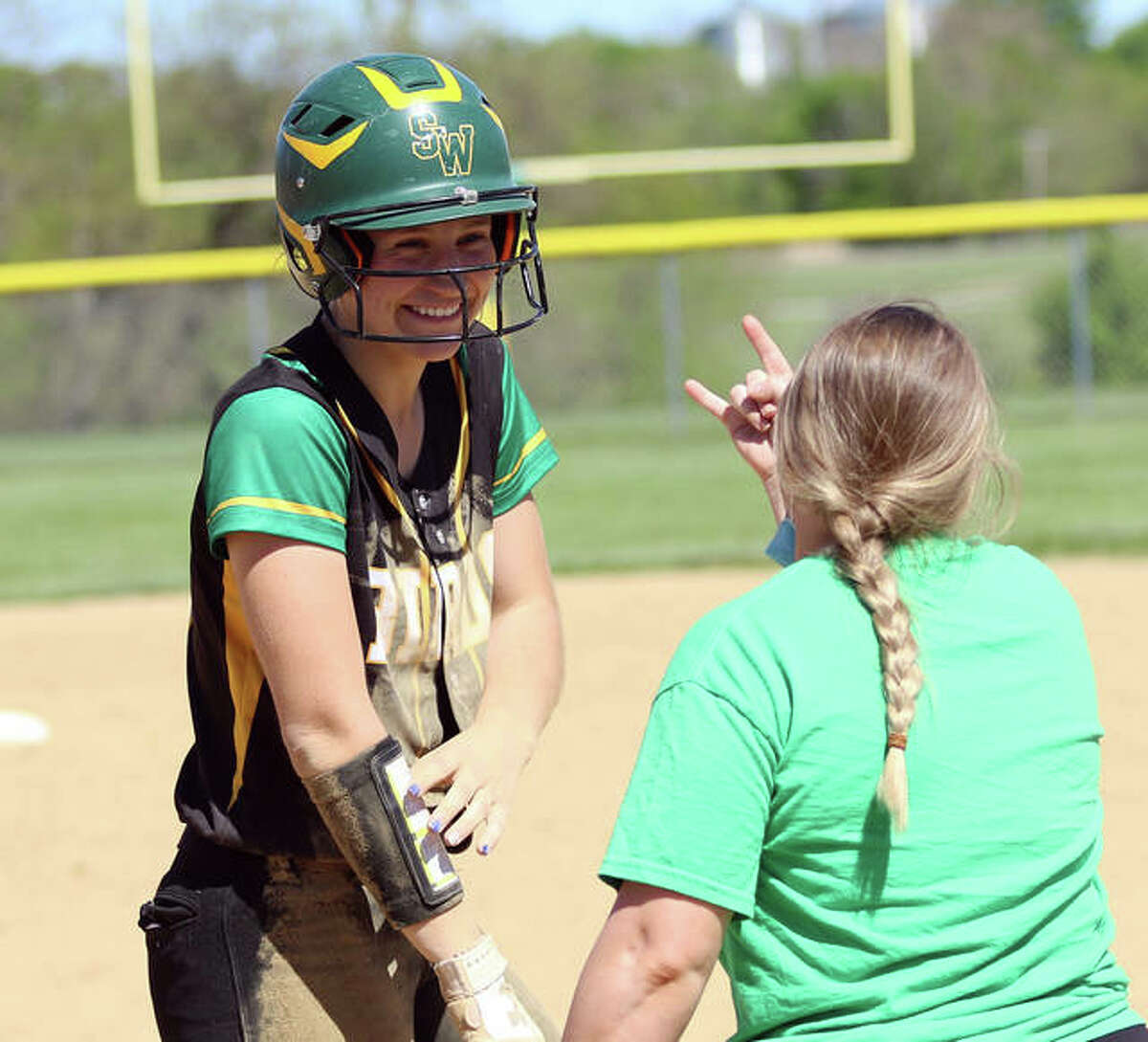 Southwestern's Megan Bailey (left) smiles at first base coach Amanda Edwards after Bailey's RBI single gave the Piasa Birds a 1-0 lead over Edwardsville in a May 12 game in Piasa.