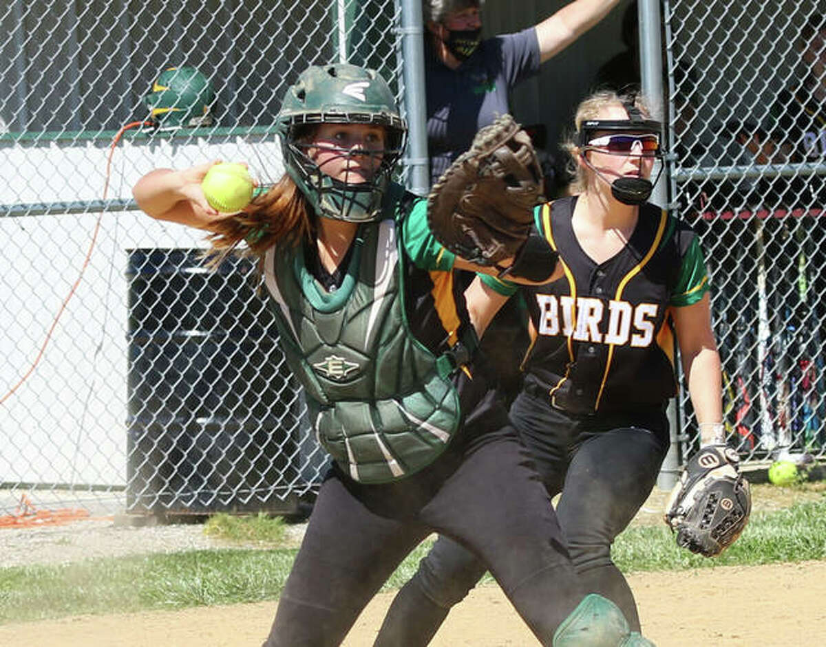 Southwestern catcher Abby McDonald (left) throws to first for an out while third baseman Bri Roloff backs up the play during a May 12 game against Edwardsville in Piasa.