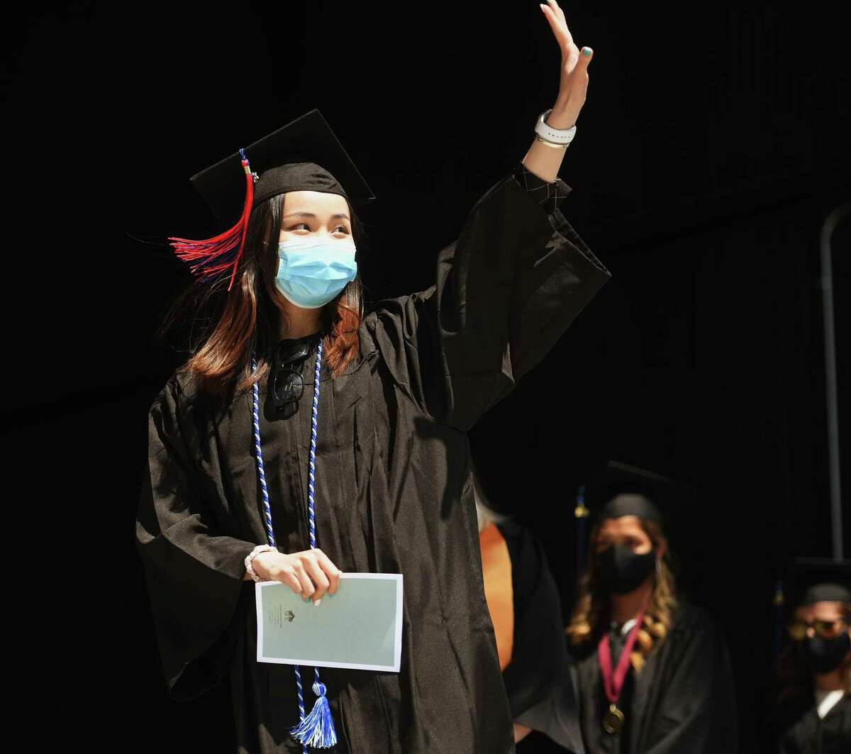 Graduate Qiuyun Huang waves to family as she crosses the stage to receive her diploma at the Norwalk Community College graduation at the new Hartford Healthcare Amphitheater in Bridgeport, Conn. on Thursday, May 20, 2021.