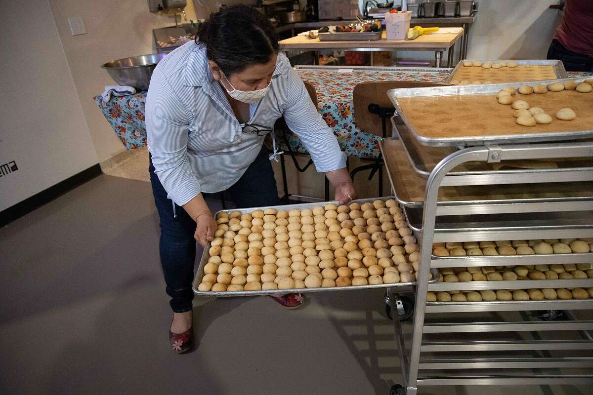 Dilsa Lugo, owner of Los Cilantro, racks some weeding cookies at a restaurant in La Cocina's Municipal Marketplace on Wednesday, May 19, 2021 in San Francisco, Calif.
