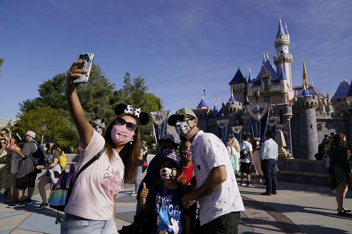 FILE - In this April 30, 2021, file photo, a family takes a photo in front of Sleeping Beauty's Castle at Disneyland in Anaheim, Calif.(AP Photo/Jae Hong, File)