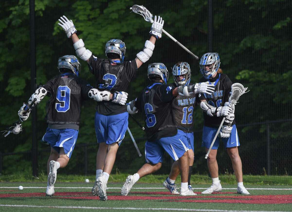 Darien players celebrate after Brady Pokorny, far right, scored with an assist from Jamison Moore (12) in the final minutes of a boys lacrosse game against New Canaan on Thursday at Dunning Field in New Canaan.