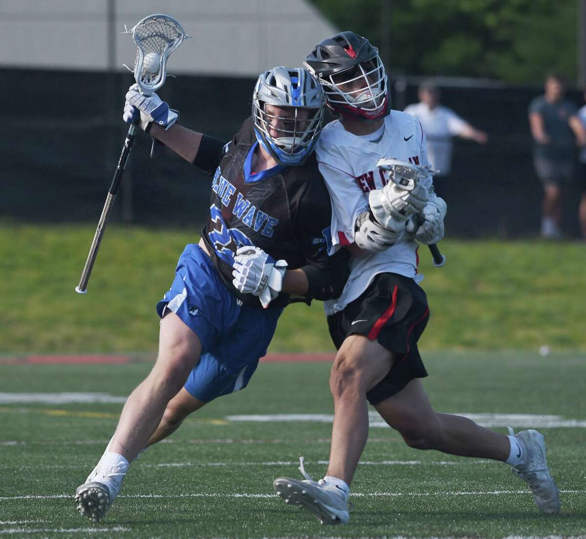 Darien's Tighe Cummiskey, left, and New Canaan's Hayden Shin collide during a boys lacrosse game on Thursday in New Canaan.