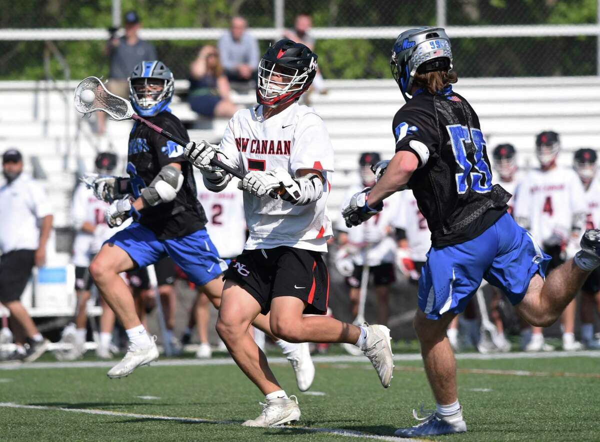 New Canaan's Hayden Shin (7) throws a pass as Darien's Jeremiah Stafford (55) closes in during a boys lacrosse game in New Canaan on Thursday, May 20, 2021.