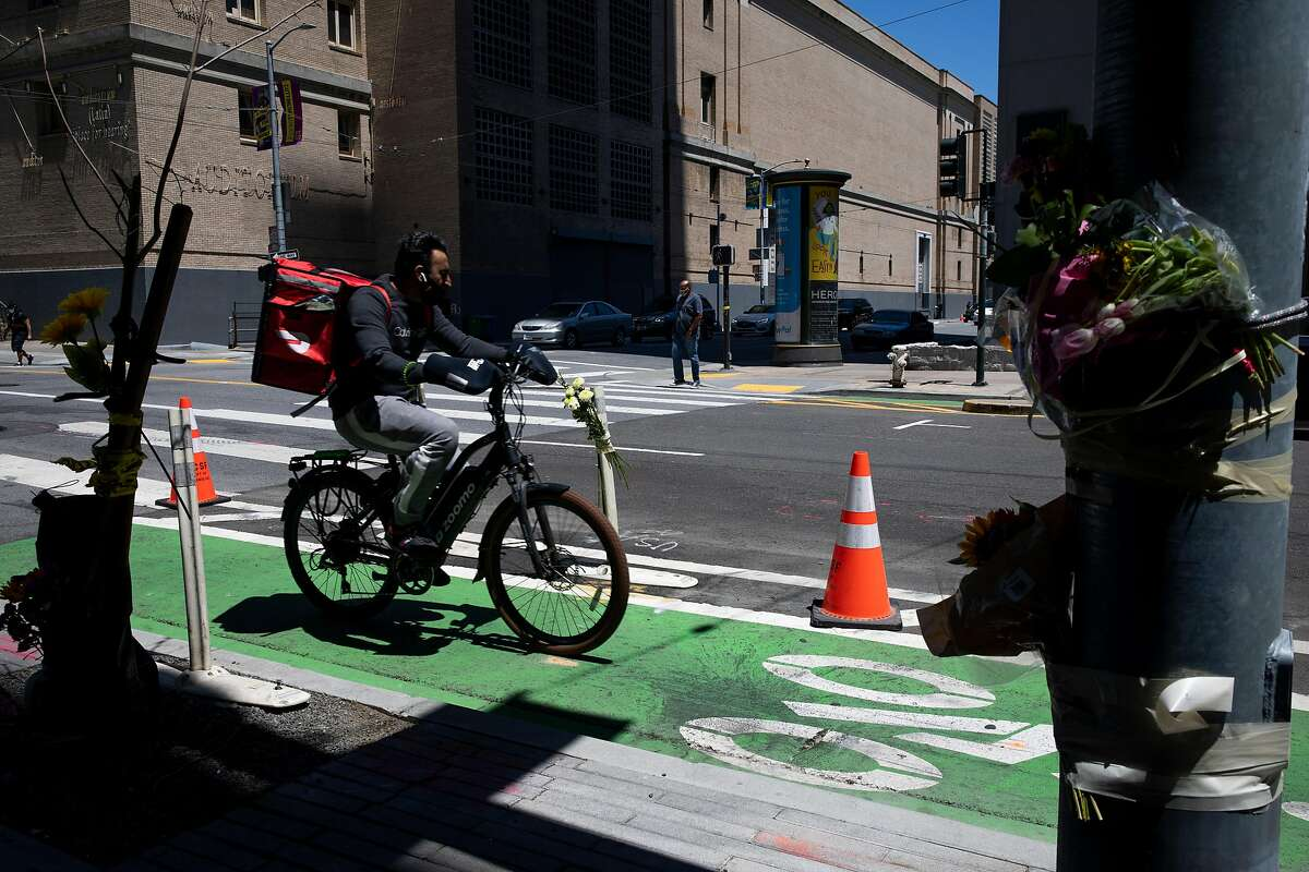 A bicyclist rides past a memorial for Lovisa Svallingson at Polk Street and Hayes Street, Thursday, May 20, 2021, in San Francisco, Calif. Svallingson, a 29-year-old software engineer, was killed in a hit-and-run crash. Officials responding to the crash at 7 p.m. Tuesday found two pedestrian victims. The crash occurred when a pickup truck collided with a sedan and then careened into the two pedestrians. One of the pedestrians was Svallingson. The driver fled the scene on foot, officials said. As of Wednesday night, police had not identified any suspects or made any arrests.