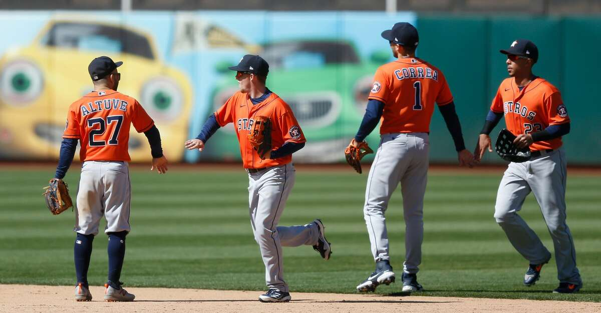 Jose Altuve #27, Myles Straw #3, Carlos Correa #1 and Michael Brantley #23 of the Houston Astros celebrate an 8-4 win over the Oakland Athletics at RingCentral Coliseum on May 20, 2021 in Oakland, California. The win lifted the Astros into first place over the Athletics in the AL West. (Photo by Lachlan Cunningham/Getty Images)