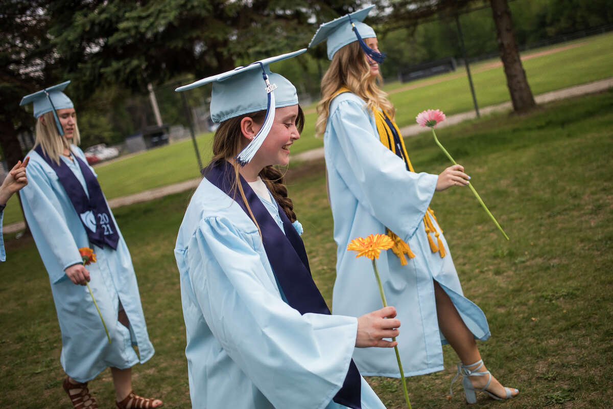 Shai Redman chats with classmates before the Meridian Early College High School Class of 2021 celebrate with a commencement ceremony Thursday, May 20, 2021 at the school in Sanford. (Katy Kildee/kkildee@mdn.net)