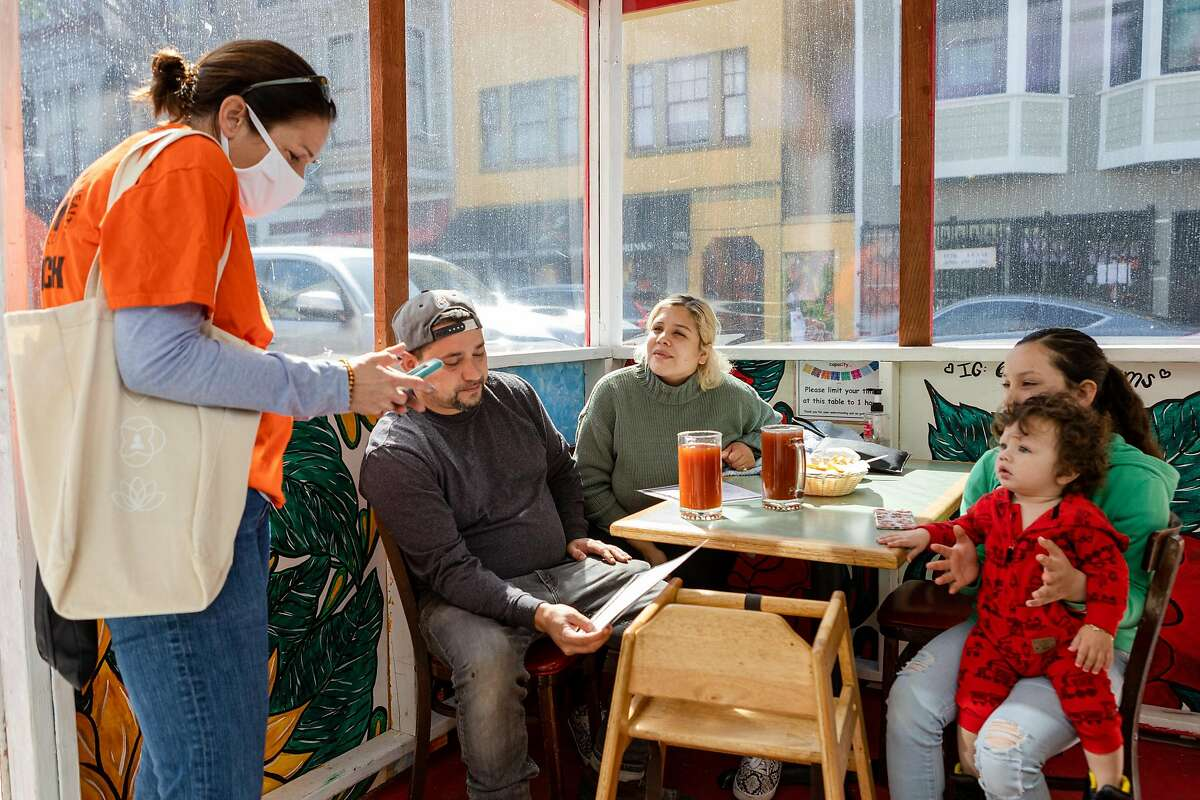 Michelle Tapia (center), Fernando Barajas, and their children have lunch while Latino Task Force and United in Health volunteer Noelle Bermingham uses her phone to register Michelle Tapia for a COVID-19 vaccine appointment on Saturday, April 10, 2021, in San Francisco, Calif.