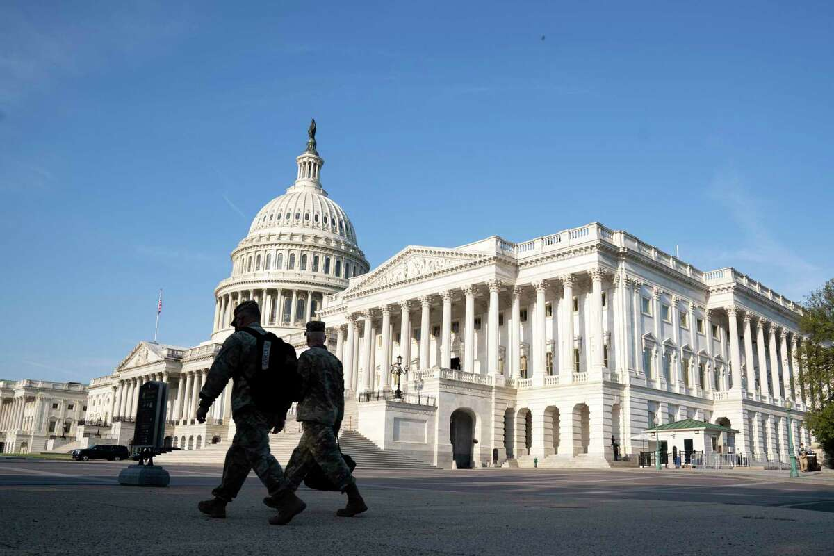 The U.S. Capitol is seen as national guard members pass by on Capitol Hill in Washington, Thursday, May 20, 2021. The House voted to create an independent commission on the deadly Jan. 6 insurrection at the U.S. Capitol, sending the legislation to an uncertain future in the Senate.