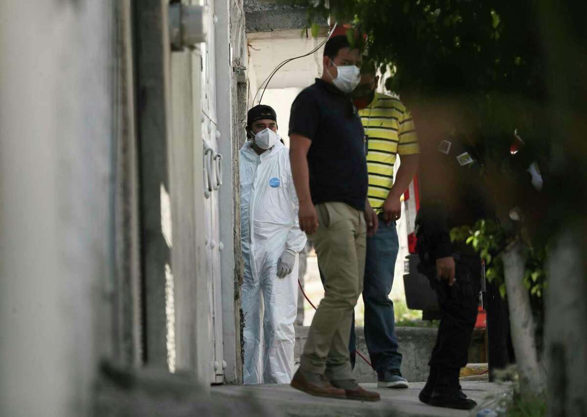 Un investigador forense permanece en la entrada de una vivienda donde la policía encontró restos óseos enterrados, en el municipio de Atizapán