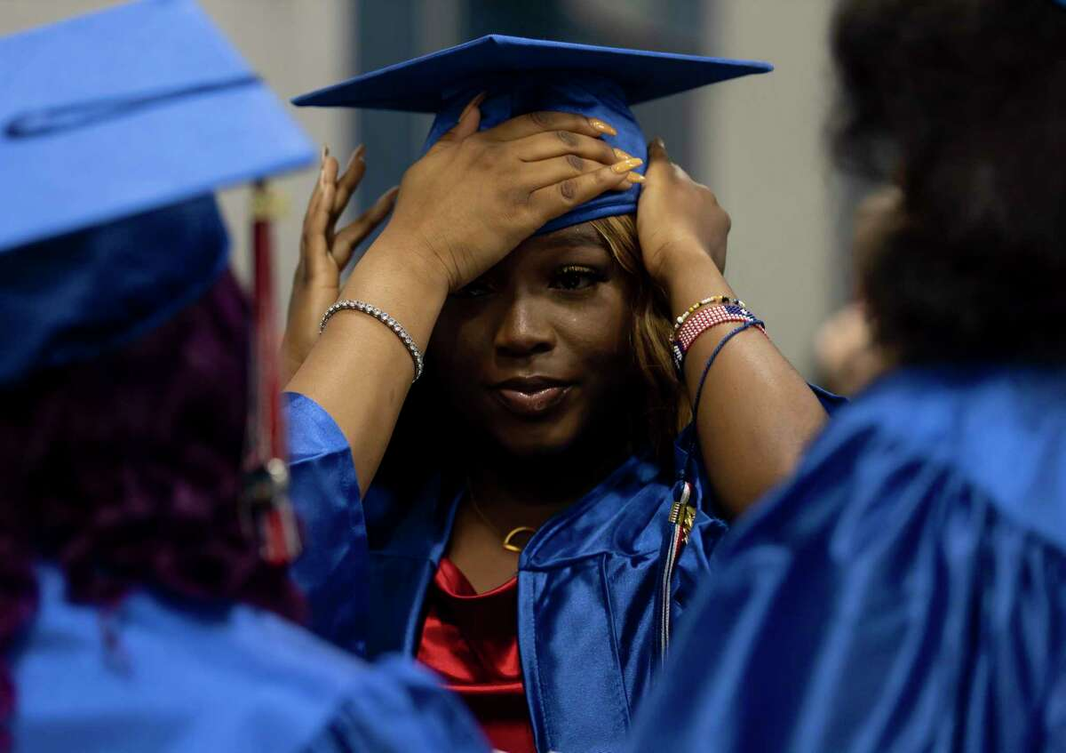 Ericka Thompson has her hat fitted with the assistance of friends before Oak Ridge High School's graduation ceremony at the Cynthia Woods Mitchell Pavilion, Thursday, May 20, 2021, in The Woodlands.