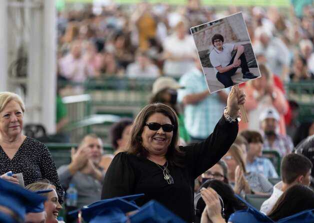 Donna McAdams stands as grandparents of graduates are called upon as she holds up an image of her grandson Cameron Barfield during Oak Ridge High School's graduation ceremony. Photo: Gustavo Huerta, Houston Chronicle / Staff Photographer / Houston Chronicle © 2021