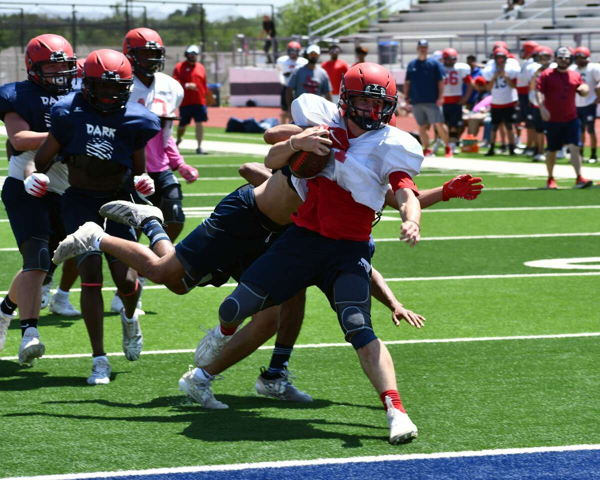 Running back Lane Carroll takes some defenders with him into the end zone for a touchdown during the Plainview football team's spring game on Thursday afternoon at Greg Sherwood Memorial Bulldog Stadium.