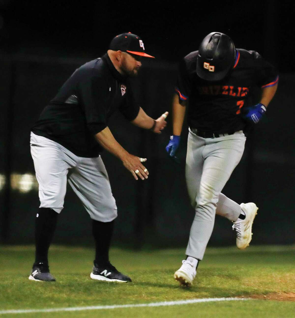 Grand Oaks' Antonio Sabala (7), shown here earlier this season with head coach Lous Ferrell, hit a walk-off two-run single Thursday as the Grizzlies defeated The Woodlands 6-5 in Game 1 of the Region II-6A quarterfinals at Humble High School.