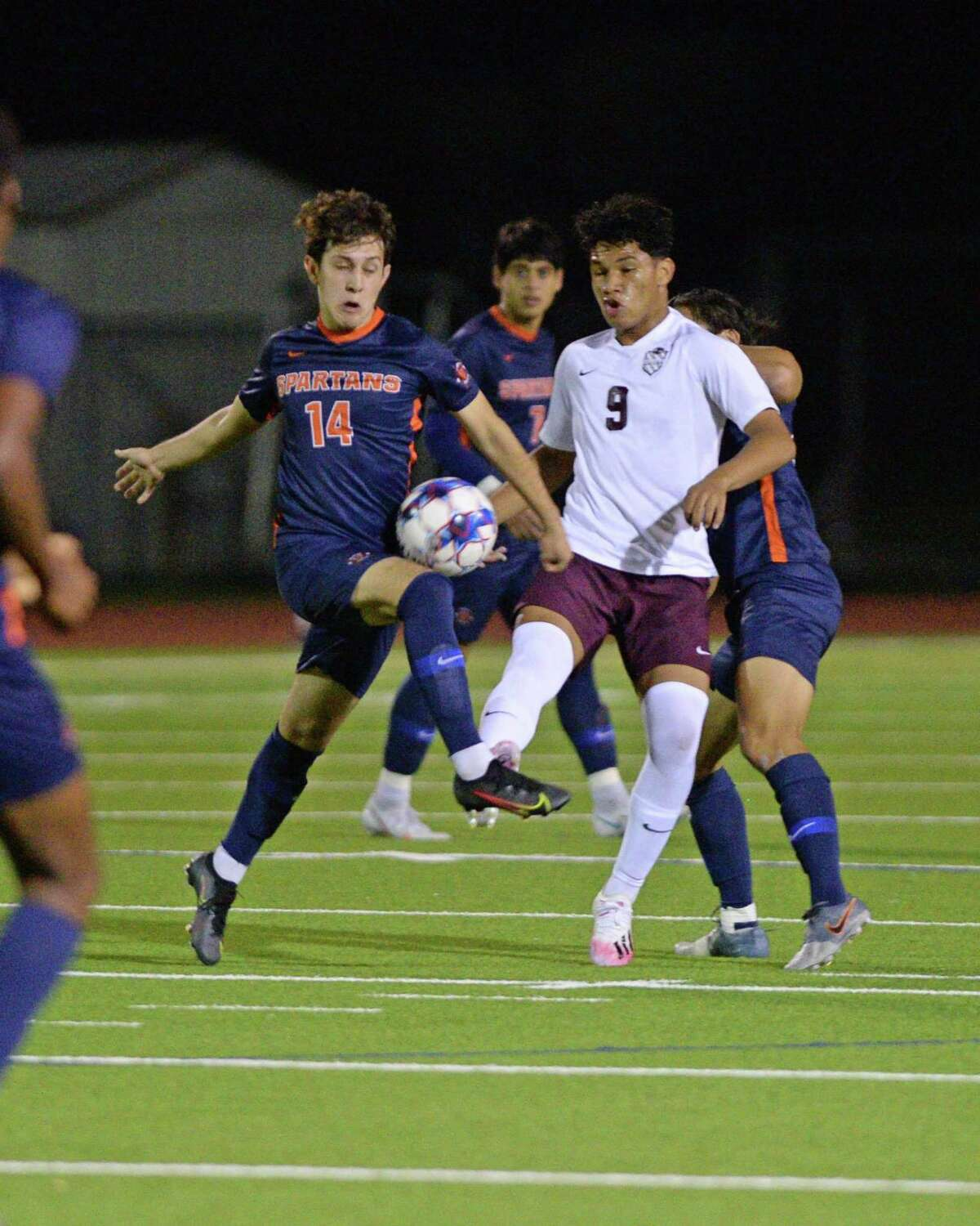 Christian Gonzalez (14) of Seven Lakes and Dany Vargas (9) of Cinco Ranch compete for a ball during the first half of a 6A-III District 19 soccer match between the Seven Lakes Spartans and the Cinco Ranch Cougars on Friday, March 12, 2021 at Seven Lakes HS, Katy, TX.