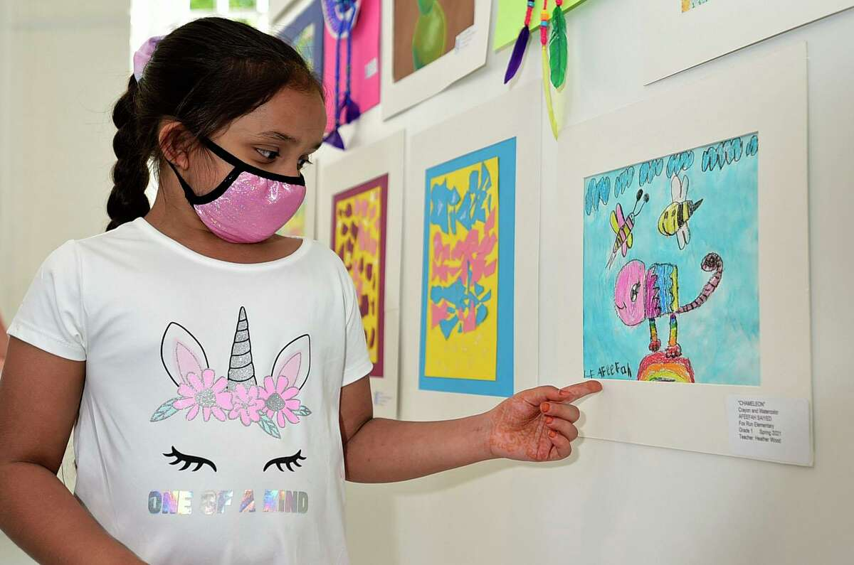 Fox Run Elementary School first grader Afeefah Saiyed points out her work at the opening night of the annual Norwalk citywide art show Thursday, May 20, 2021, at the Art Space in Norwalk, Conn. This is the first year it will be at the Norwalk Art Space.