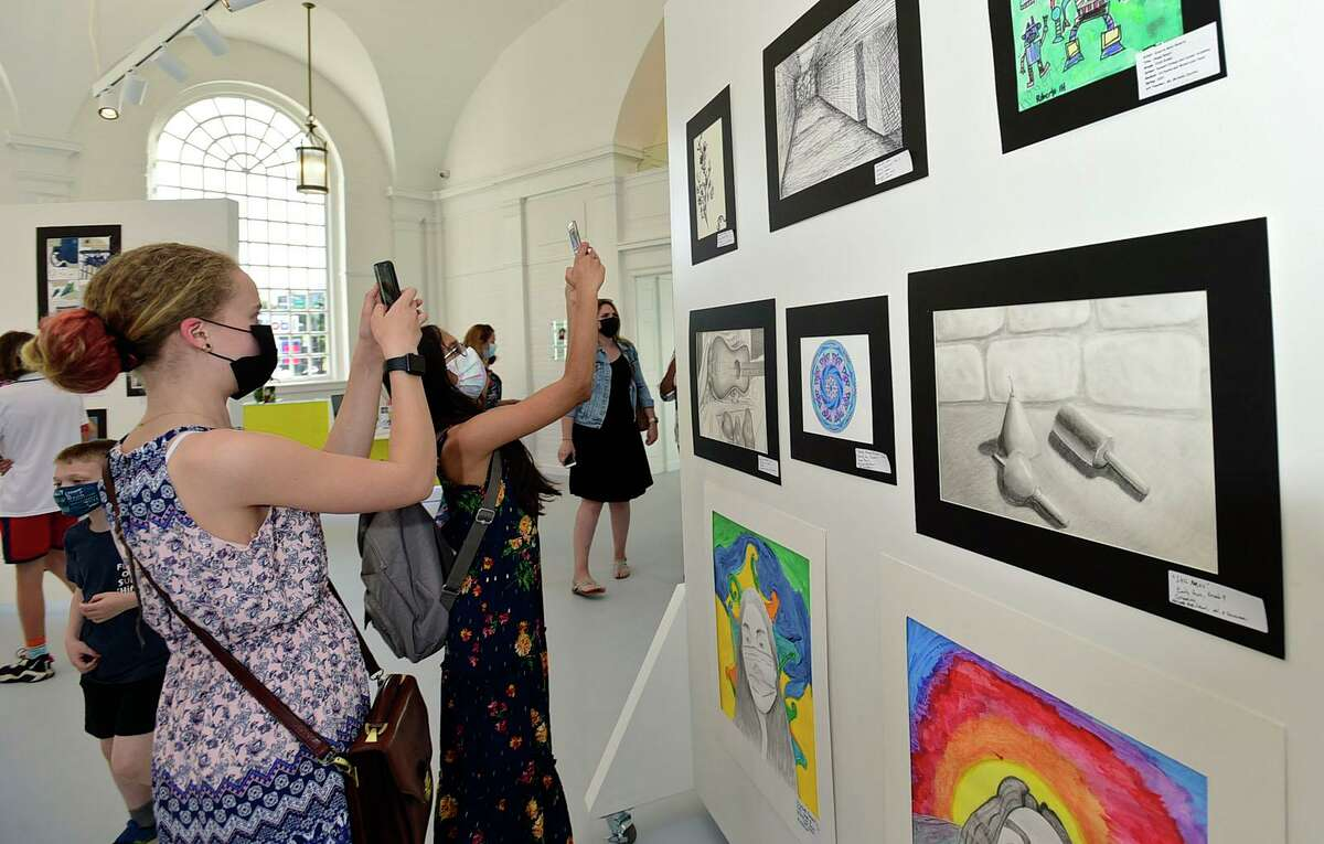 West Rocks Middle School 7th graders Rylie Peterson and Yana Divakaran take photos during the opening night of the annual Norwalk citywide art show Thursday, May 20, 2021, at the Art Space in Norwalk, Conn. This is the first year it will be at the Norwalk Art Space.