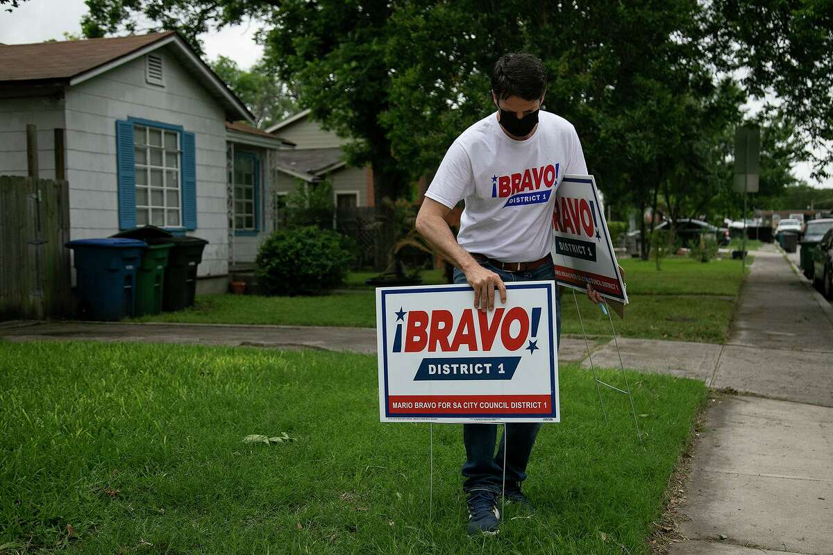 Bravo places one of his signs in a yard.