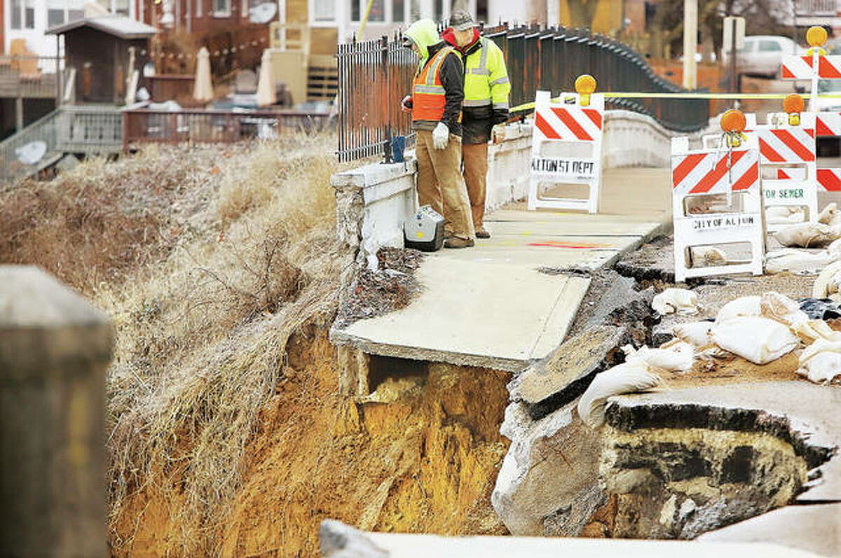 In this file photo, contractors and Alton Public Works and Park and Recreation workers inspect Riverview Drive where the water-damaged wall along the bluff collapsed and fell off. After a year and a half of discussions, federal and state officials on Friday morning confirmed Alton will receive more than $3.7 million to address the problem.