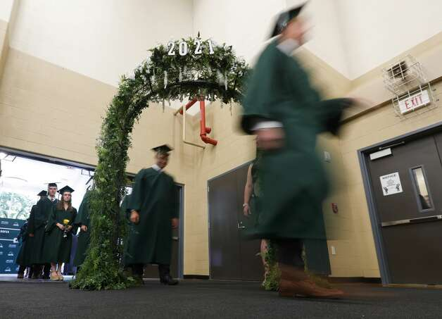 John Cooper students walk through an archway during a graduation ceremony, Friday, May 21, 2021, in The Woodlands. Photo: Jason Fochtman/Staff Photographer