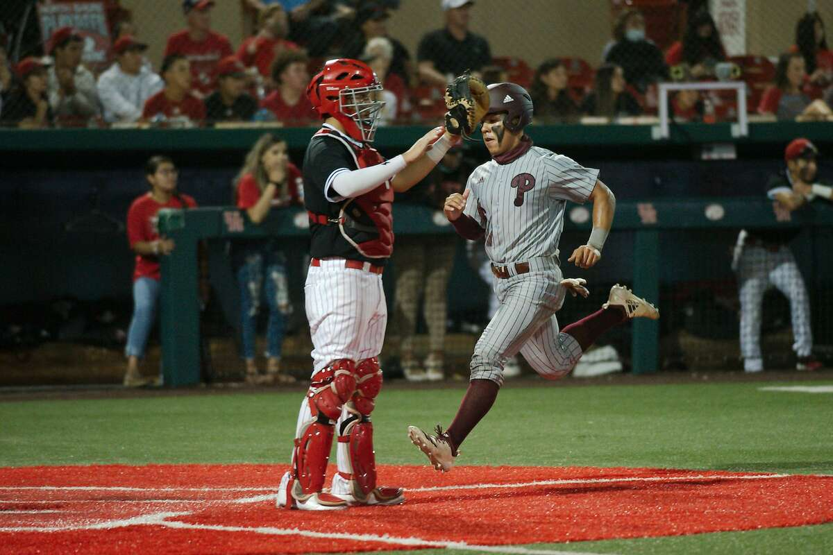 North Shore's Alex San Miguel (21) looks for the throw as Pearland's Cameron Ponce (6) crosses home plate Thursday, May 20 at the University of Houston.