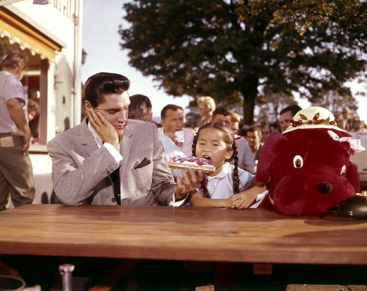 """American singer, actor Elvis Presley and Philippine actress Vicky Tiu on the set of """"It Happened at the World's Fair"""" directed by Norman Taurog. (Photo by Sunset Boulevard/Corbis via Getty Images)"""