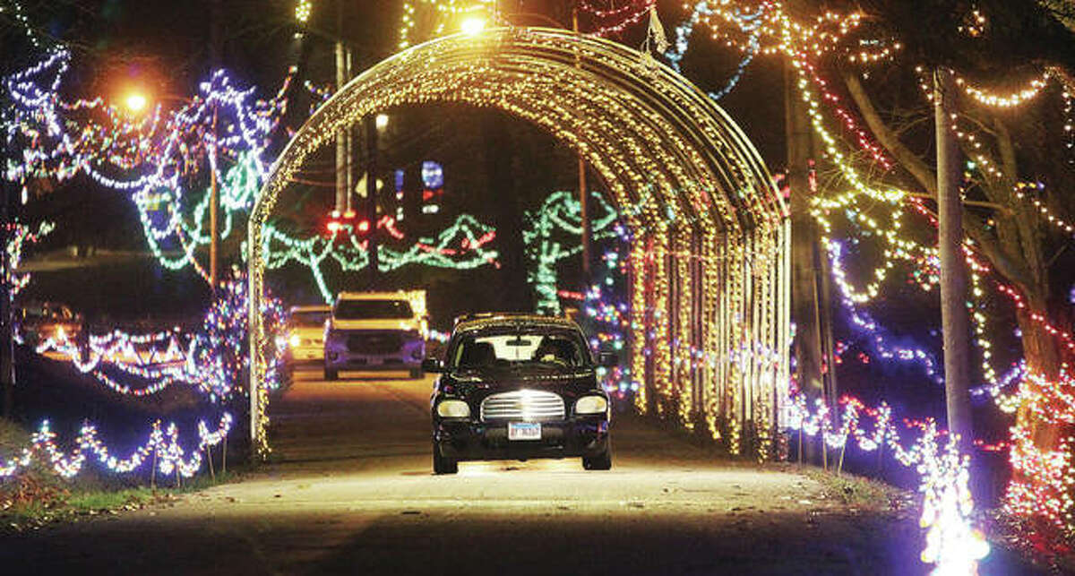 A car goes through a light tunnel at the start of Christmas Wonderland, the annual holiday light display put on by The Grandpa Gang in Alton's Rock Spring Park during the opening night on Friday, Nov. 27. The This year the Grandpa Gang has increased donations to area community organizations following record attendance during the 2020 holiday event, with nearly $65,000 was distributed to 53 organizations.