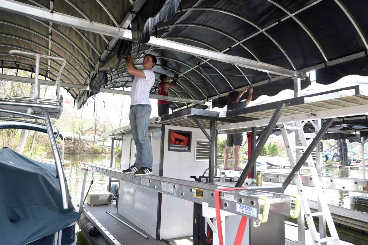 Echo Bay Marina workers install canopies over boat slips in April 2021 in Brookfield, Conn.