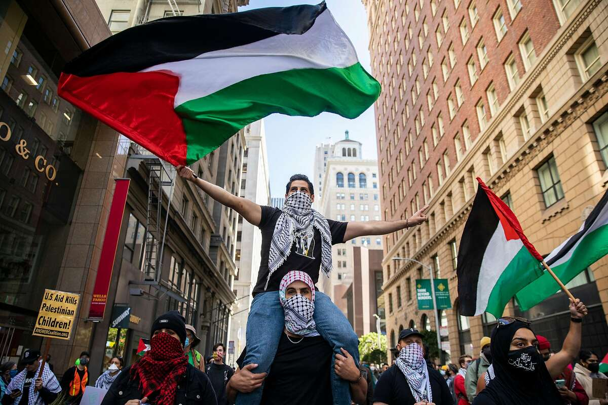 Mohamed Dahleh waves the flag of Palestine while on the shoulders of Munir Abughannam in solidarity with hundreds of protesters outside the Israeli Consulate, Tuesday, May 18, 2021, in San Francisco, Calif.