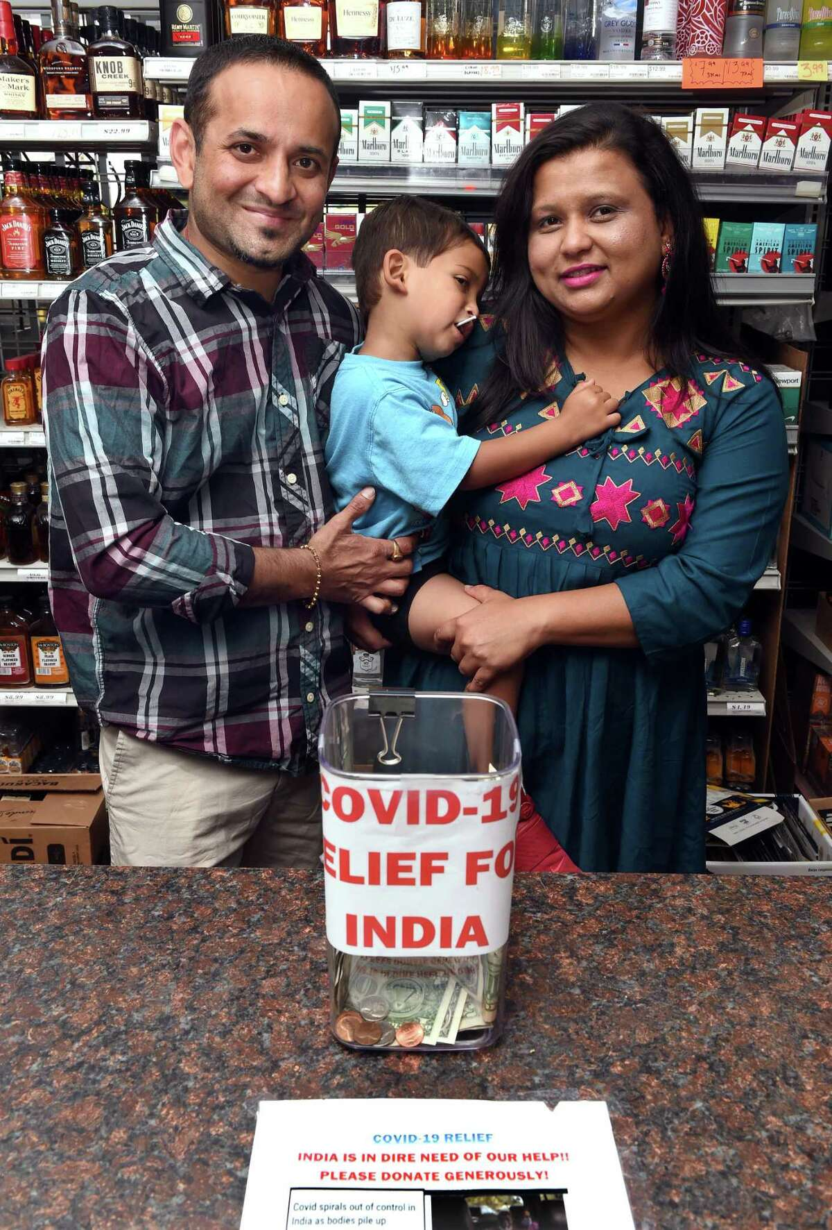 Keyur Patel, left, with his wife, Nital, and son, Ved, 31/2, behind the counter of one of the family's package stores, Town & Country Liquors in Bethany, May 19, 2021, where he is raising funds and matching donations for COVID-19 relief in India.