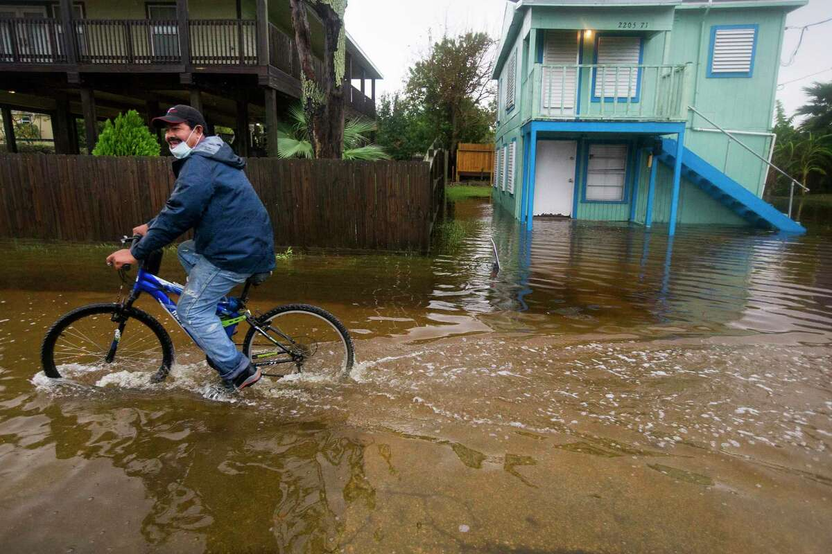 Rafael Juarez rides his bicycle through a street flooded by Tropical Storm Beta as he makes his way home from the store Monday, Sept. 21, 2020 in Galveston.