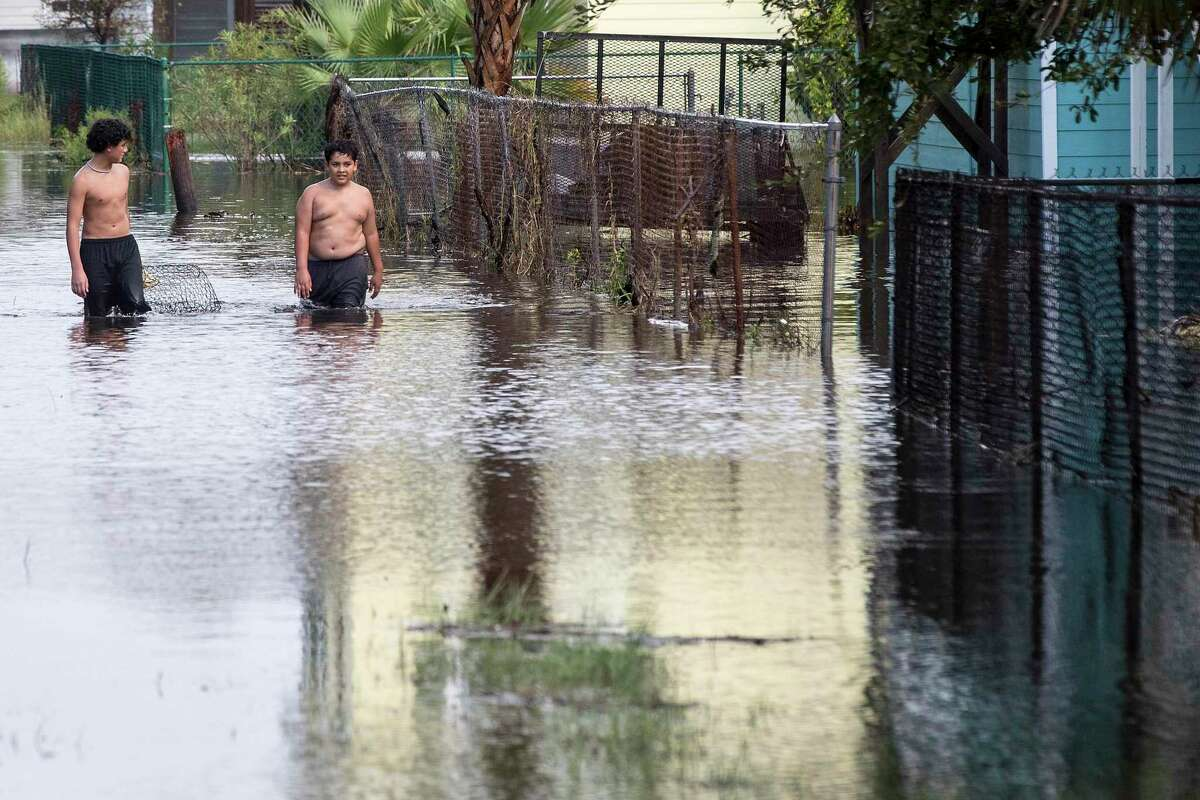 Wilmer Murillo, left, and his brother, Maxxi, walk along a fence line in floodwaters from Tropical Storm Beta Tuesday, Sept. 22, 2020 in Galveston.