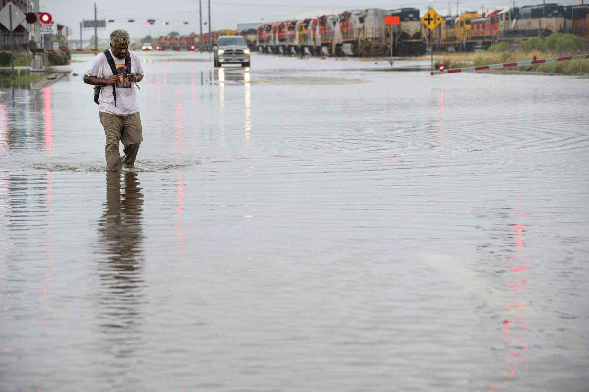 A man walks through floodwaters from Tropical Storm Beta along Harborside Drive Tuesday, Sept. 22, 2020 in Galveston.