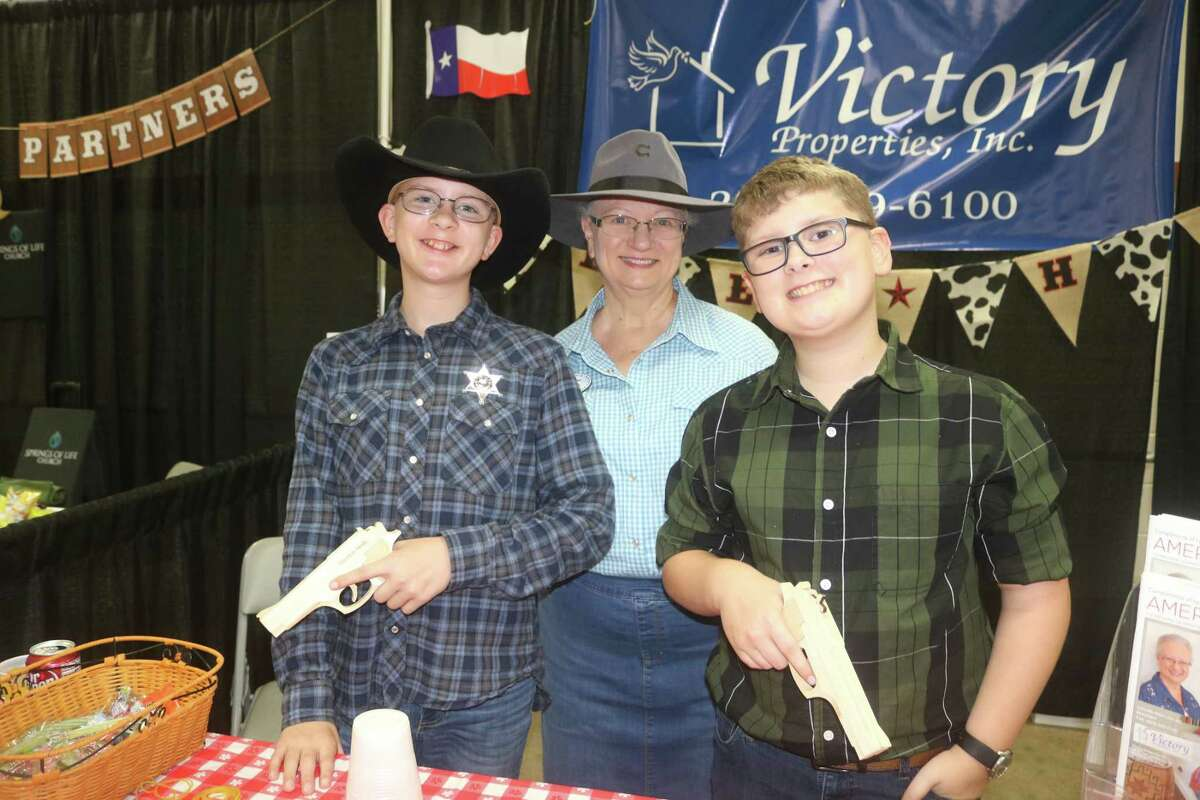 Cowboy hat-wearing grandma Lynnette Elder joined her rubber-band-gun-slinging duo of Kane and Dillon Elder for some fun at the Village Properties booth.