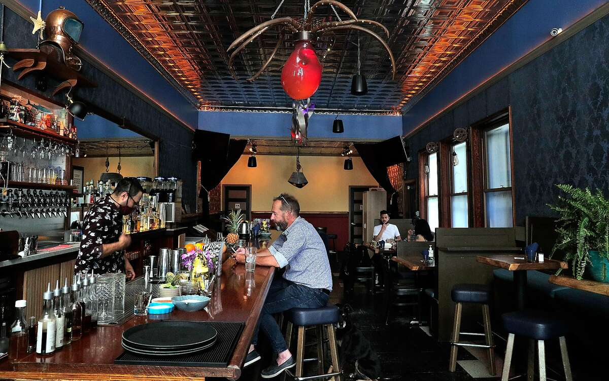 Bartender Ramon Piñon, left, mixes a drink for John Lister at Sea Star Bar, which reopened for business for several days in San Francisco on May 9 with capacity limits. The state will allow bars and other businesses to lift all restrictions June 15.