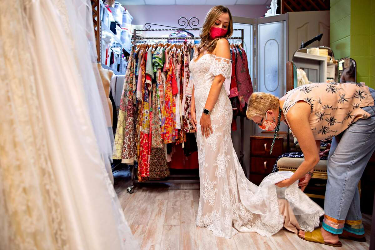 Seamstress and shop owner Kim Northrop helps Natalie Griffin with her gown during her final wedding dress fitting at Betty's Girl Couture in Napa, Calif. Friday, May 7, 2021. Natalie Griffin and fiance Jeff Scott are having a very small wedding May 15, followed by a big celebration in October.