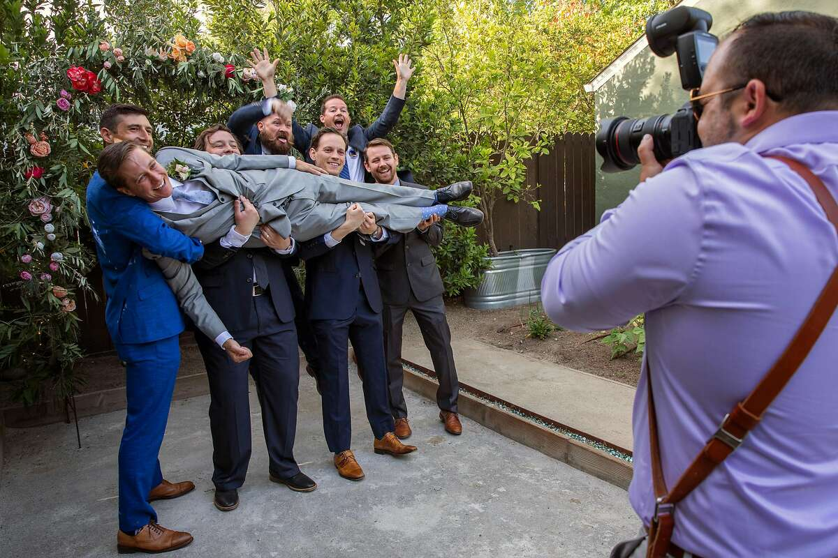 Jeff Scott is lifted by friends and family as their wedding photographer Vincent Piombo takes photos, Saturday, May 15, 2021, in Napa, Calif. Scott married Natalie Griffin in the backyard of a friend's home.