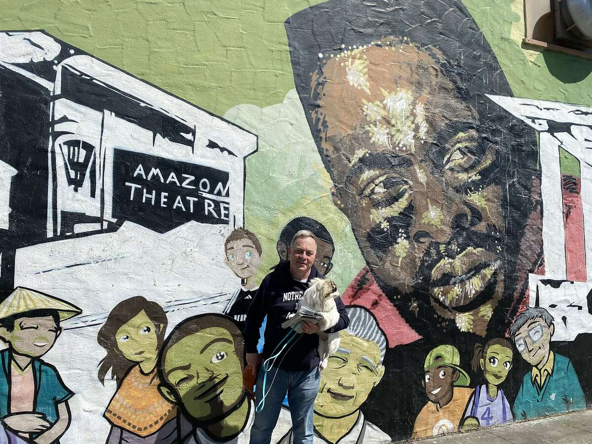 Kevin Fisher-Paulson and his dog Queenie pose in front of a mural at Cordova Market & Deli in San Francisco.