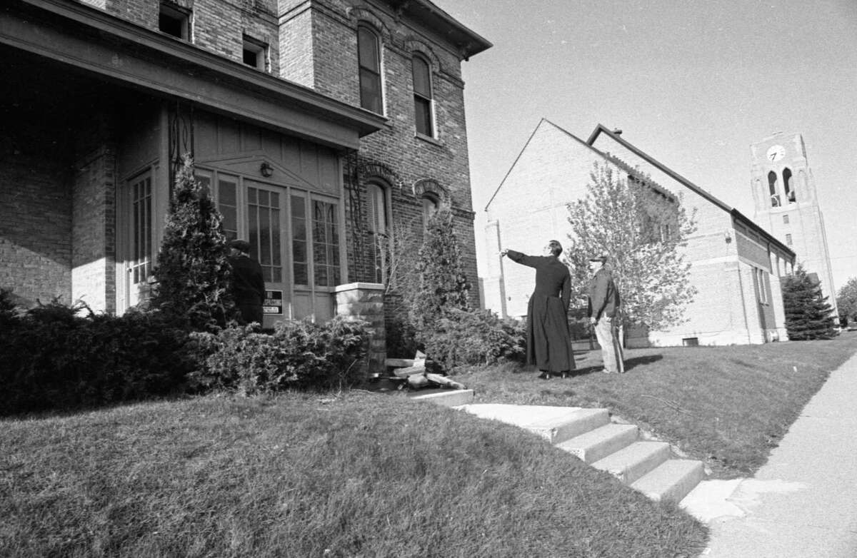 Father Clarence Smolinski discusses the St. Joseph Catholic Church rectory with a workman in mid-May 1981 shortly before the former rectory was demolished. (Manistee County Historical Museum photo)