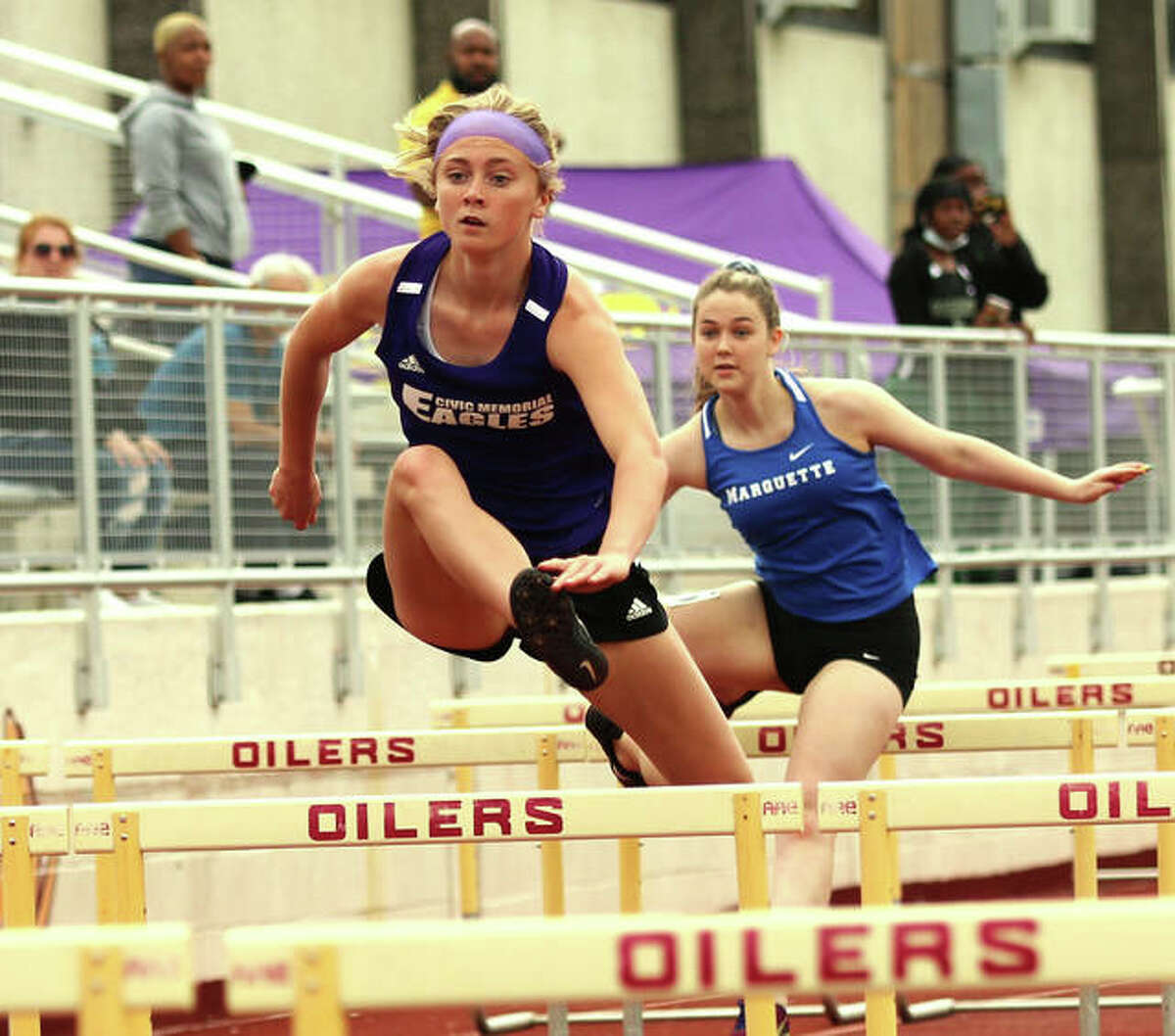 CM sophomore Bella Dugger (left) clears a hurdle again of Marquette Catholic's Tristan Fraley in Dugger's victory in the 100-meter hurdles Monday at the Madison County Small-Schools girls track meet at Memorial Stadium in Wood River.