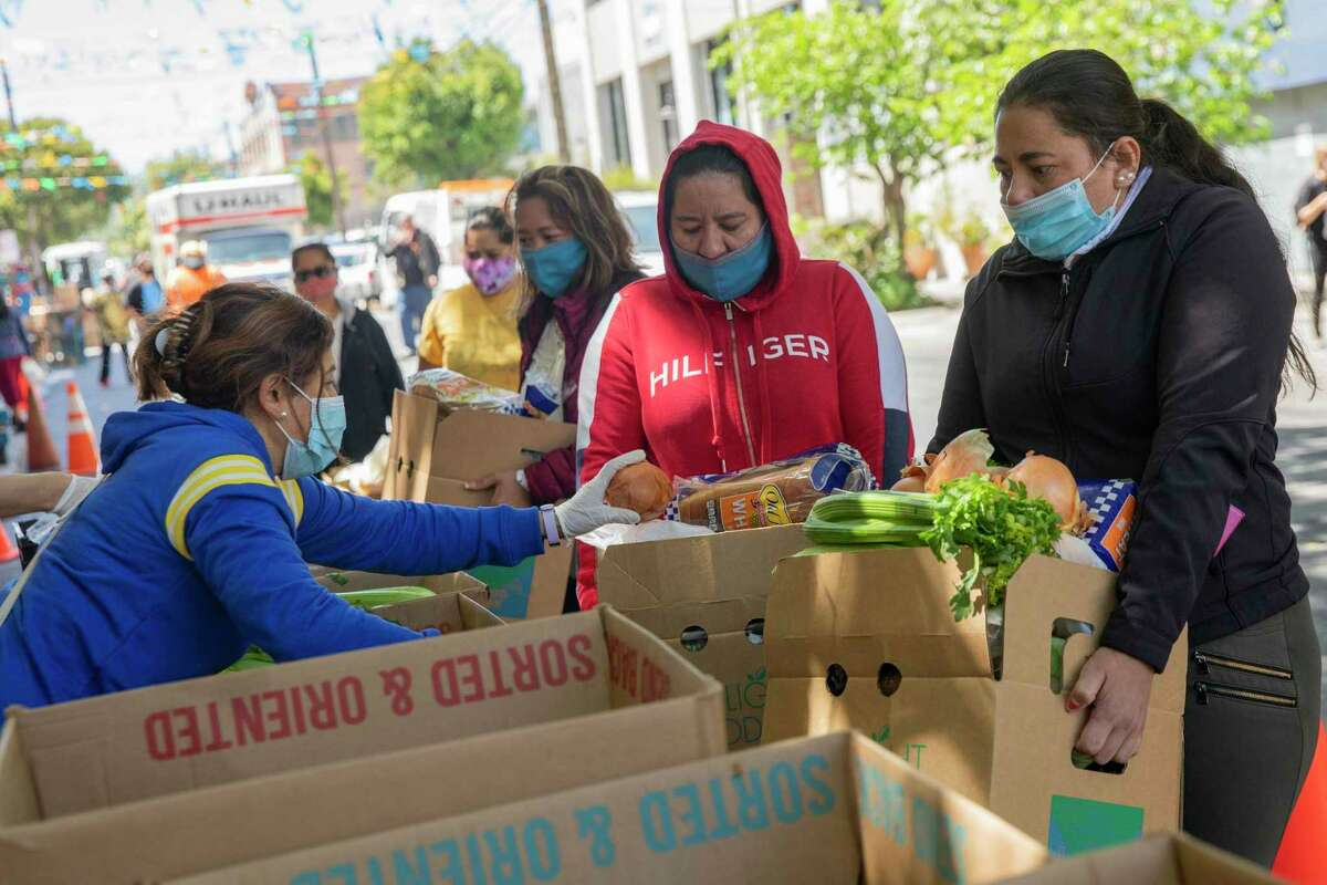 Belkin Herrera (right) and her sister Dilenia Hernandez receive a box of groceries in May from the Mission Food Hub in San Francisco. Approximately 608,000 households in the Bay Area are not earning enough income to cover the costs of housing, food, medical and childcare, among other daily essentials, according to a United Ways of California study.