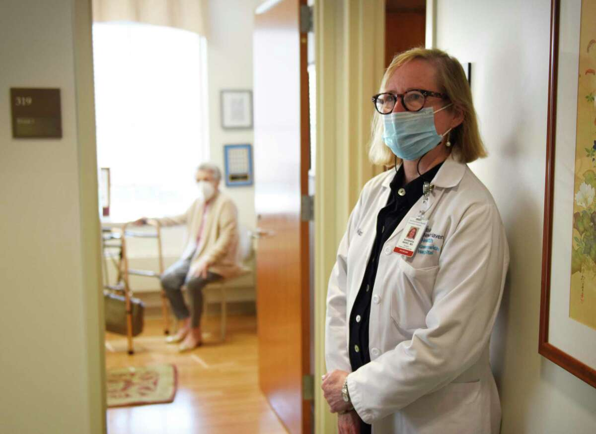 Dr. Barbara Ward, right, medical director at the Greenwich Hospital Breast Center, stands in a hallway of the center on Wednesday, May 19, 2021. In the background, at left, is Greenwich resident Inge Pelke, a breast cancer survivor. Ward performed the cancer surgery on Pelke in 2014 and has seen Pelke for annual check-ups every year since then.
