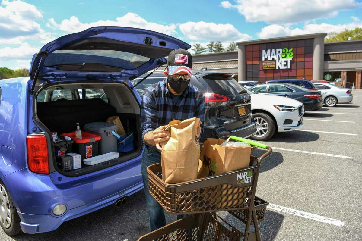 A man wearing two masks, and goggles, loads groceries in New York. If wearing a mask feels more comfortable, stick with it. As we return to a pre-pandemic normal, it's going to take time to adjust.