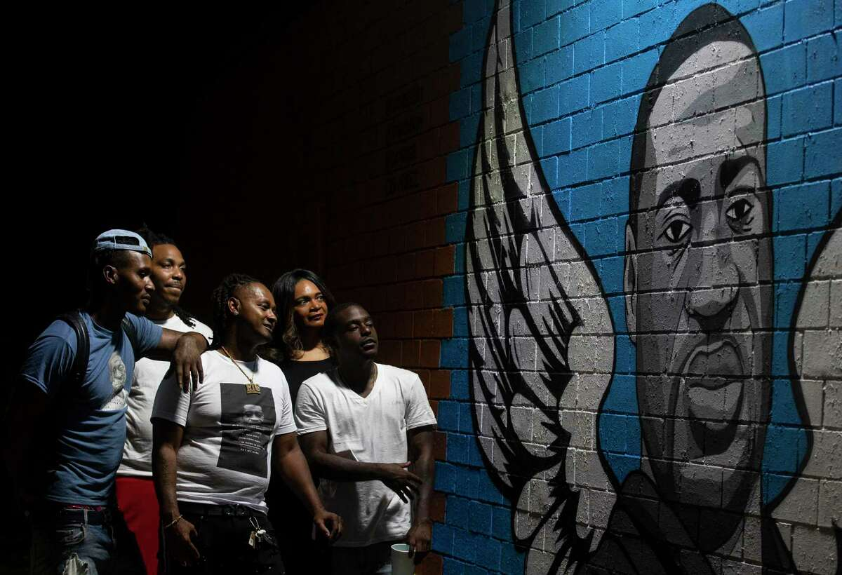 """Chris """"Gutta"""" Hutchins, left to right, Leonard """"Junebug"""" McGowen, Terrance """"Magnet2damoney"""" Jones, Tiffany Cofield, and Calvin Masters pose for a photograph in front of the mural honoring former Houston resident George Floyd in the Third Ward on Wednesday, June 3, 2020, in Houston. Floyd died while in custody of four Minneapolis Police officers last week."""