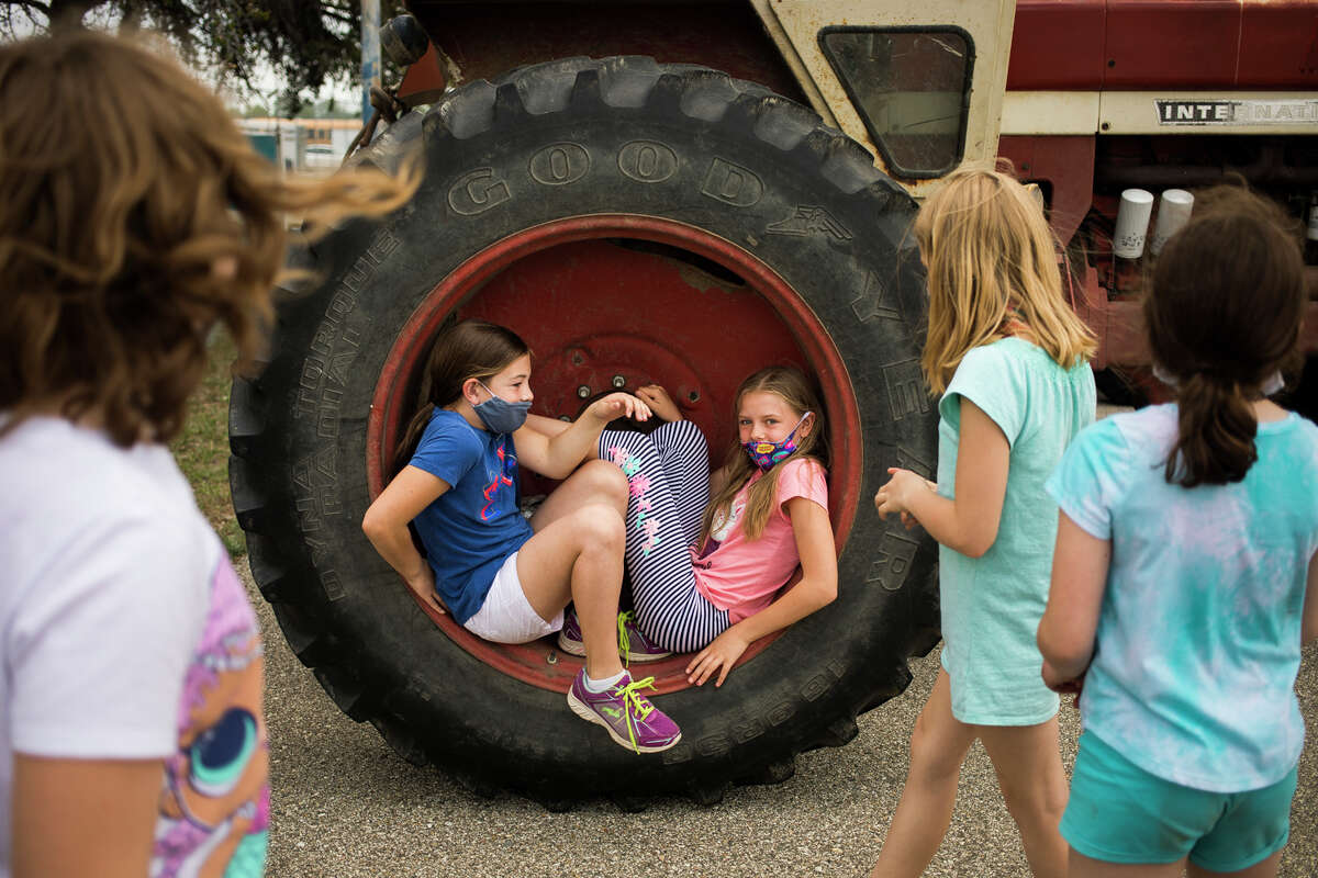 Coleman Elementary School fourth graders Olivia Hegel, 10, right, and Abby Hayes, 9, left, sit on the tire of a tractor as Coleman High School students take questions about their tractors from Coleman Elementary School students after participating in